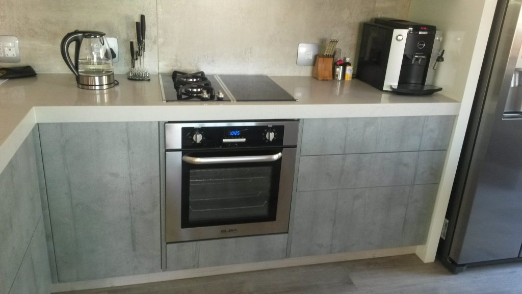 Handleless kitchen in Seno HiGloss Cashmere, Hemlock Nordique Kaindl and London Grey Caesarstone