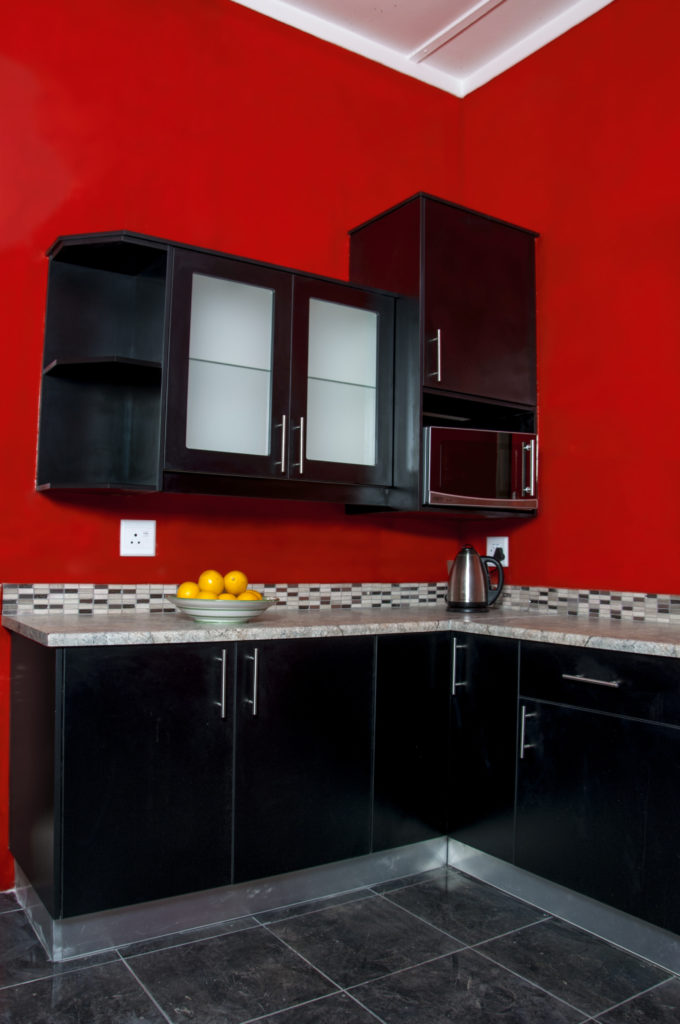 Black Melamine doors with Formica work tops against red walls