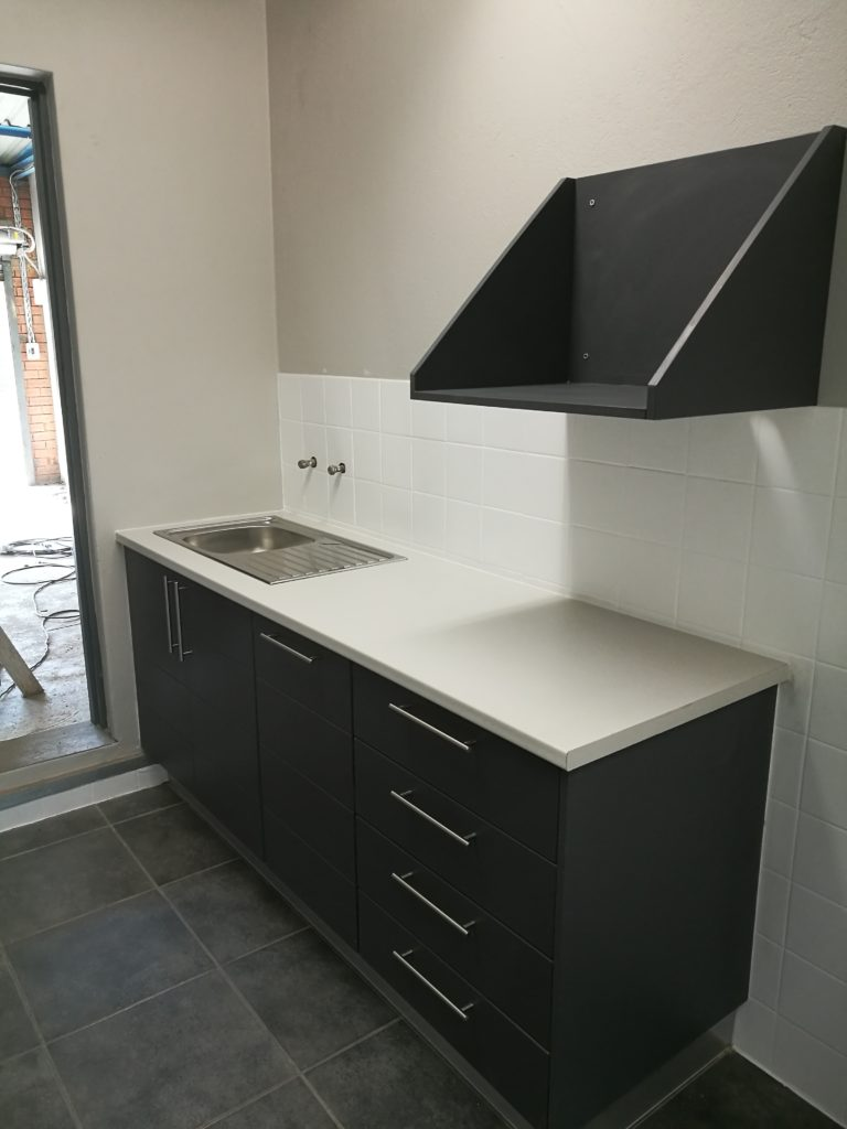 Charcoal wrap with horizontal groove and 'White Myriad' Formica top