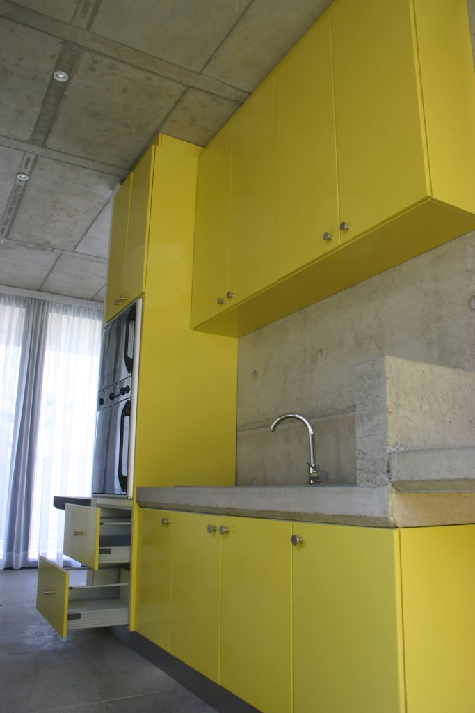 Bright yellow sprayed doors with concrete work surfaces